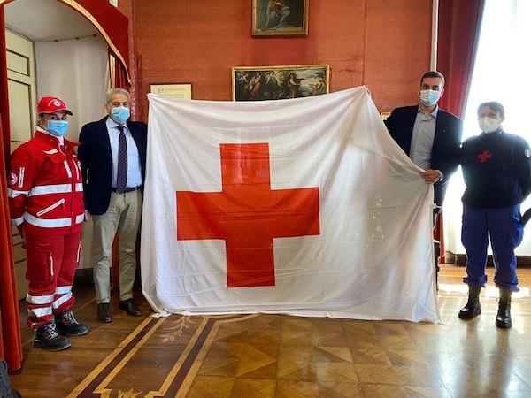 Bandiera della Croce Rossa esposta sulla facciata di Palazzo dei Priori e di Palazzo del Drago
