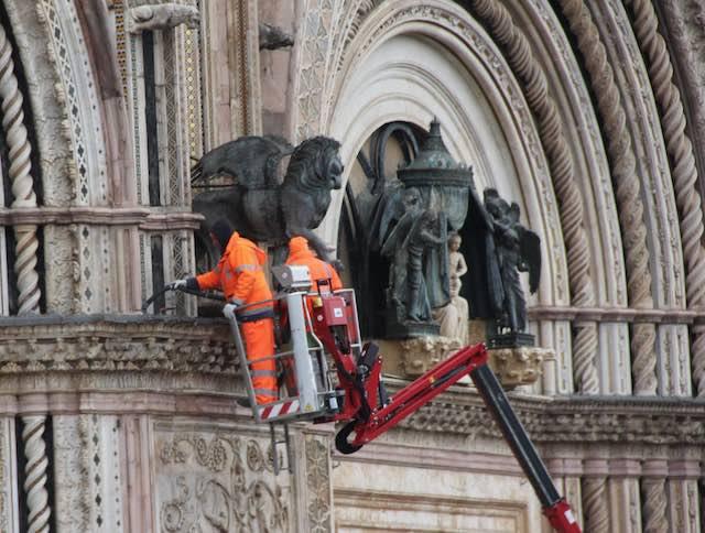 Tecnici al lavoro per pulire la facciata del Duomo